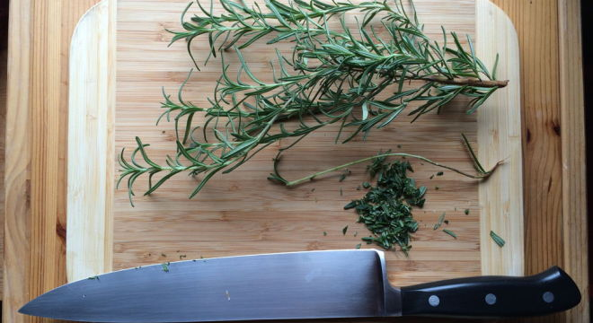Chopping rosemary.